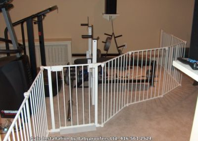 White baby gate installed to keep children from workout equipment.
