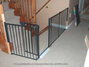 Dark green baby gate designed to restrict access to stairs going up and down.
