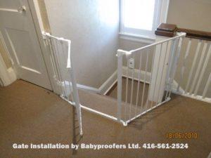 White baby gate around top of stairs.