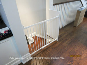 White baby gate installed at top of stairs where wall extends out.