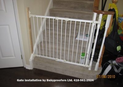 Typical white baby gate installed between wall and railing post.