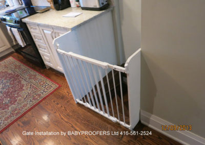 White baby gate installed where the stairs start past both walls.