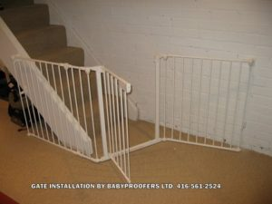 White baby gate installed at bottom of stairs where opening is slightly irregular.