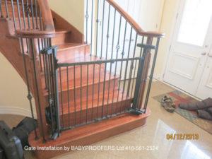 Black baby gate installed between two metal railings using clamps.