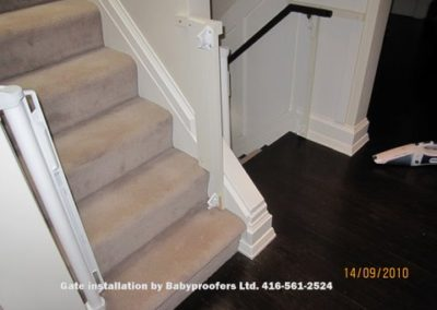 Retractable baby gates installed on both sides of stairs.