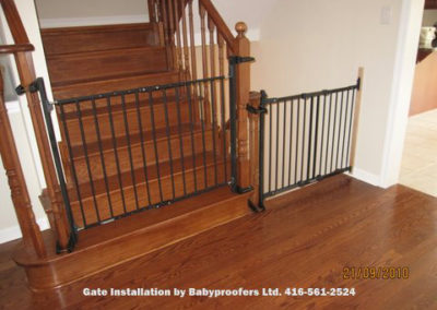 Dark green baby gates installed across two openings using newel post clamps.
