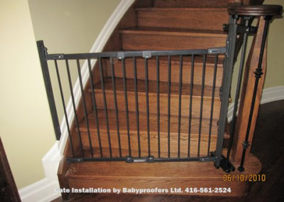 Baby gate attached to metal railings using specialty clamps.