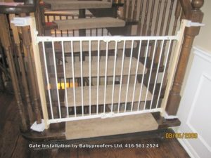 White safety gate installed with clamps instead of mounting holes.
