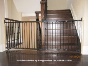 Two large black baby gates across stair openings.