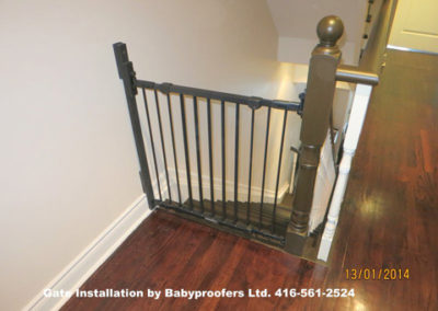 Typical simple baby gate installed between wall and newel post.