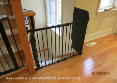 Black baby gate installed with fixed panel on the right.
