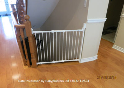 Typical installation of a white baby gate between a fixed wall and the newel post of a railing.