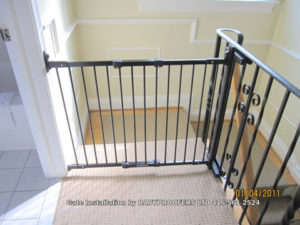 Baby gate installed between wall and metal railing.