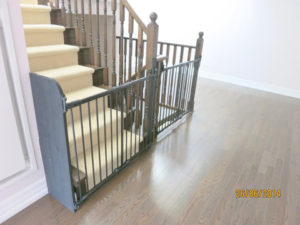Two grey baby gates installed with one using extension panel on the left.