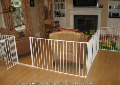 White baby gate installed around large area.