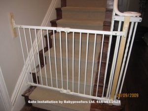 White baby gate attached to metal railings with special clamps.