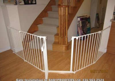 White baby gate installed around stairs and hallway.