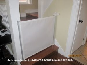 Retractable baby gate installed at the bottom of the stairs.