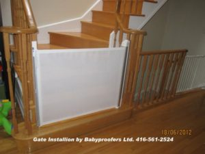 Retractable white baby gate installed at the bottom of the stairs between railings.