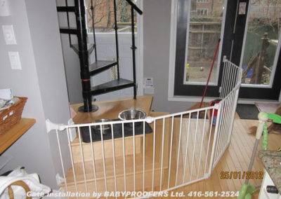Irregular shaped white baby gate surrounding base for spiral stairs.