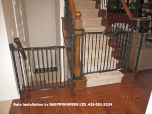 Dark green safety gate installed using mounting clamps.