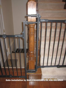 Details of mounting brackets for baby gate attached to newel post.