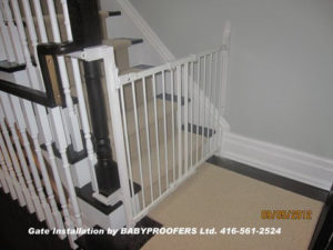 White baby gate installed using newel post clamps.