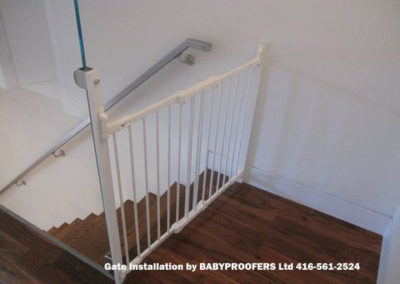 White baby gate attached to glass wall.