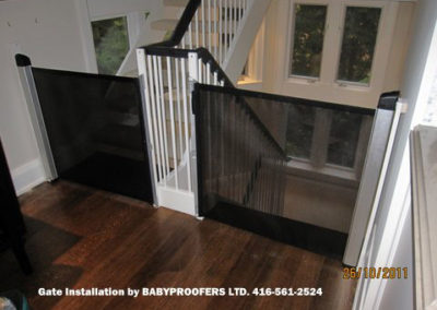 Black retractable baby gates installed on either side of stair openings.