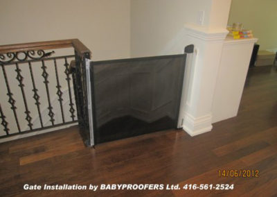 Retractable black baby gate installed at the top of some stairs.
