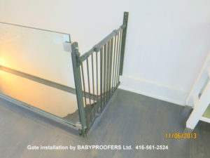 Baby gate installed between a glass rail and fixed wall.