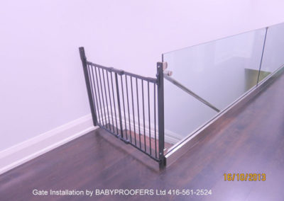 Baby gate installation between glass partition and wall.