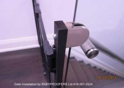 Close up of glass clamps for securing baby gate.