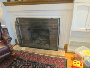 Black child safe fire screen installed in front of natural fireplace.