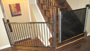Black combination baby gate with slider on the right and swing gate on the left.