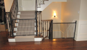 Pair of black baby gates installed between wall and railings.